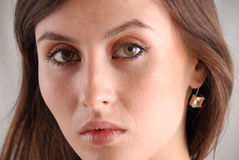 Portrait of brown-eyed young woman, close-up. Hard look of dark-haired girl gazing intently, full face, gauzy earring in small ear, expressive eyebrows and brown Royalty Free Stock Images