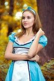 Portrait of brown-haired girl. In a suit in the nature of Alice in Wonderland Royalty Free Stock Images