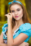 Portrait of brown-haired girl. In a suit in the nature of Alice in Wonderland Royalty Free Stock Photos
