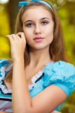 Portrait of brown-haired girl. In a suit in the nature of Alice in Wonderland Stock Photos