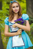 Portrait of brown-haired girl. In a suit in the nature of Alice in Wonderland with a bouquet of flowers Stock Images