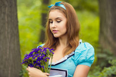 Portrait of brown-haired girl. In a suit in the nature of Alice in Wonderland with a bouquet of flowers Stock Image