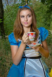 Portrait of brown-haired girl. In a suit in the nature of Alice in Wonderland tea party on Royalty Free Stock Photography