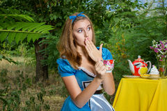 Portrait of brown-haired girl. In a suit in the nature of Alice in Wonderland tea party on Royalty Free Stock Images