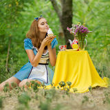 Portrait of brown-haired girl. In a suit in the nature of Alice in Wonderland tea party on Stock Image