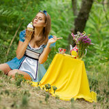 Portrait of brown-haired girl. In a suit in the nature of Alice in Wonderland tea party on Royalty Free Stock Photos