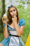 Portrait of brown-haired girl. In a suit in the nature of Alice in Wonderland tea party on Royalty Free Stock Photo