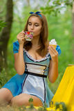 Portrait of brown-haired girl. In a suit in the nature of Alice in Wonderland tea party on Stock Photos