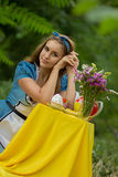 Portrait of brown-haired girl. In a suit in the nature of Alice in Wonderland tea party on Stock Photo