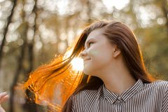 Portrait of a brown-haired girl whose sunset sunlight shimmers in her hair. A young lady with a confident smile looks straight royalty free stock images