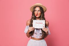 Portrait of brunette beautiful woman 20s wearing straw hat holding pms calendar, isolated over pink background in studio. Portrait of brunette beautiful woman royalty free stock image