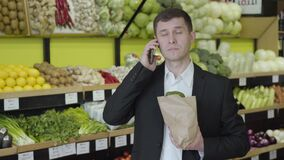 Portrait of brunette brown-eyed Caucasian man talking on the phone in grocery. Adult confident guy holding pack with