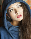 Portrait of a brunette with brown eyes. Brown eyed girl in the hood with the gaze Royalty Free Stock Photos