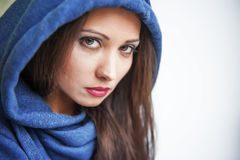 Portrait of a brunette with brown eyes. Brown eyed girl in the hood with the gaze Stock Images