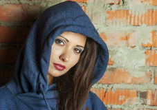 Portrait of a brunette with brown eyes. Brown eyed girl in the hood with the gaze Stock Image