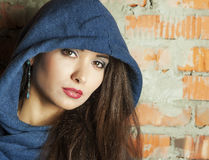 Portrait of a brunette with brown eyes. Brown eyed girl in the hood with the gaze Royalty Free Stock Photography