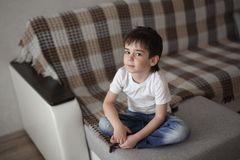 Portrait of a brunette child boy with gray eyes. In a real home interior stock images