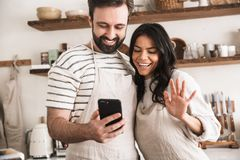 Portrait of brunette couple hugging together and holding smartphone while cooking in kitchen at home. Portrait of brunette couple men and women 30s wearing stock photography