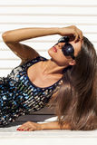 Portrait of a brunette in a dress with paillettes. Portrait of a tanned brunette wearing sunglasses Royalty Free Stock Image