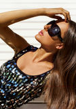 Portrait of a brunette in a dress with paillettes. Portrait of a tanned brunette wearing sunglasses Stock Photography