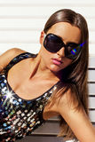 Portrait of a brunette in a dress with paillettes. Portrait of a tanned brunette wearing sunglasses Stock Images