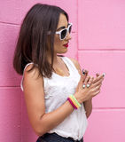 Portrait of a brunette fashion girl lifestyle outdoors woman stands in front  pink wall Royalty Free Stock Image