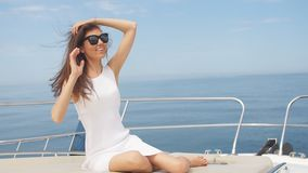 Portrait of brunette female posing over sea marine background on sailing boat