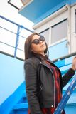 Portrait of brunette female in sunglasses over blue stairs. Portrait of brunette female in sunglasses on a blue stairs Stock Photo