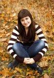 Portrait of brunette girl in the autumn park. Stock Image