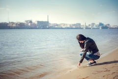 Portrait of  brunette girl in casual clothes drawing on the sand Royalty Free Stock Photography