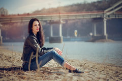 Portrait of  brunette girl in casual clothes sitting on the beac Royalty Free Stock Photo
