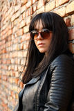 Portrait of a brunette girl in dark leather clothes next to a br. Ick wall at sunset Stock Photography