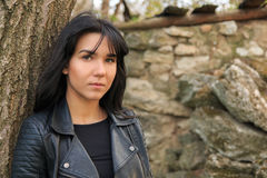 Portrait of a brunette girl in dark leather clothes next to the. Stone wall Royalty Free Stock Images