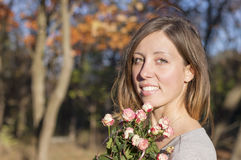 Portrait of a brunette girl holding miniature roses Royalty Free Stock Photos