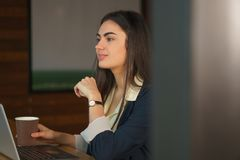 Portrait brunette girl with a laptop and coffee thinks before making an important decision stock images