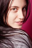 Portrait of brunette girl with long hair over pink stock photography
