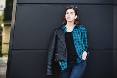 Portrait of brunette girl wearing leather jacket standing outdoors in the city against the black urban wall Stock Photos