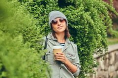 Portrait of a brunette hipster relaxing in a city park with coff Stock Image
