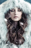 Portrait of a brunette lady wearing hooded fur coat. Portrait of a brunette woman wearing hooded fur coat Royalty Free Stock Images