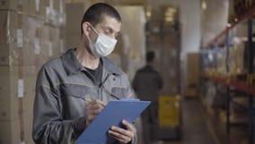 Portrait of brunette man in face mask filling out bill of landing in warehouse. Professional Caucasian male employee