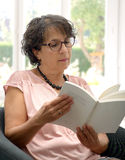 Portrait of brunette mature woman reading a book Royalty Free Stock Photos