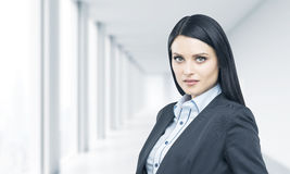 A portrait of brunette professional in formal suit. Bright modern office in blur on the background. stock photo