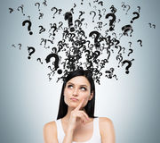 A portrait of brunette with questioning expression and question marks above her head. Stock Photography