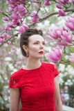 Portrait of a brunette in a red dress in a garden of blooming magnolias stock photos