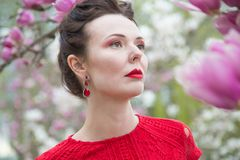 Portrait of a brunette with a red lipstick lips in a red dress near a blooming magnolia stock photo