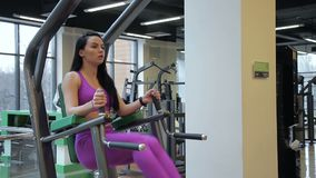 The portrait of brunette sportswoman who is training her abs doing leg raises in the gym. The young lady in purple sportwear is holding the handles of the stock video footage