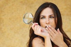 Portrait of brunette woman. Portrait of young attractive amazed woman holding loupe and covering her mouth with hand against yellow background Stock Photo