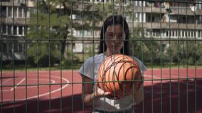 Portrait of brunette teen girl with basketball ball looking at the camera standing behind the mesh fence at the. Portrait of brunette woman with basketball ball stock footage