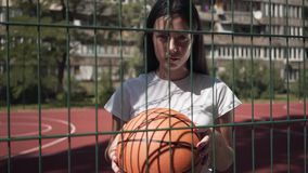 Portrait of brunette woman holding basketball ball looking at the camera standing behind the mesh fence at the. Portrait of brunette woman with basketball ball stock video footage