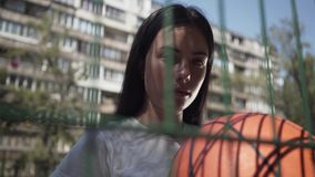 Portrait of brunette girl holding basketball ball looking at the camera standing behind the mesh fence at the basketball. Portrait of brunette woman with stock footage